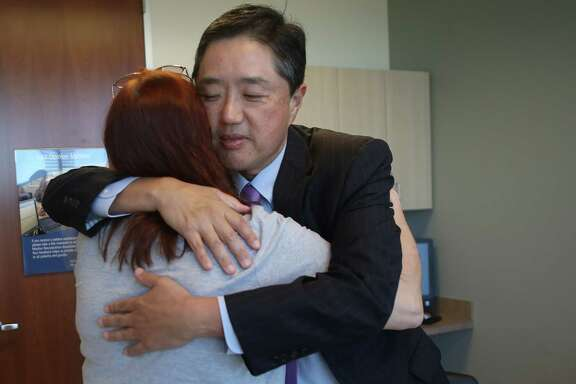 Dr. Dong Kim, the head of neurosurgery at Memorial Hermann Hospital, hugs Gina Sharp, of Baytown, at the end of a consultation regarding Sharp's brain aneurysm, Tuesday, Dec. 6, 2016, in Houston. Dr. Kim's research has discovered a gene mutation linked to brain aneurysms. ( Mark Mulligan / Houston Chronicle )