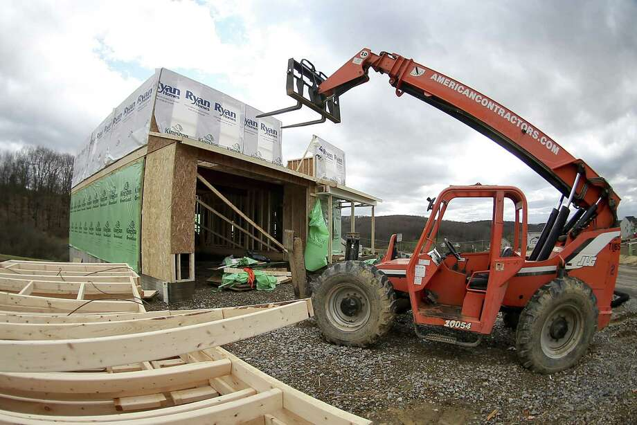 A forklift is parked in front of one of the houses under construction in a housing plan in Zelienople, Pa. U.S. builders broke ground on fewer homes in March, but the pace of construction so far this year remains stronger than in 2016, according to the Commerce Department. Photo: Keith Srakocic /Associated Press / Copyright 2017 The Associated Press. All rights reserved.