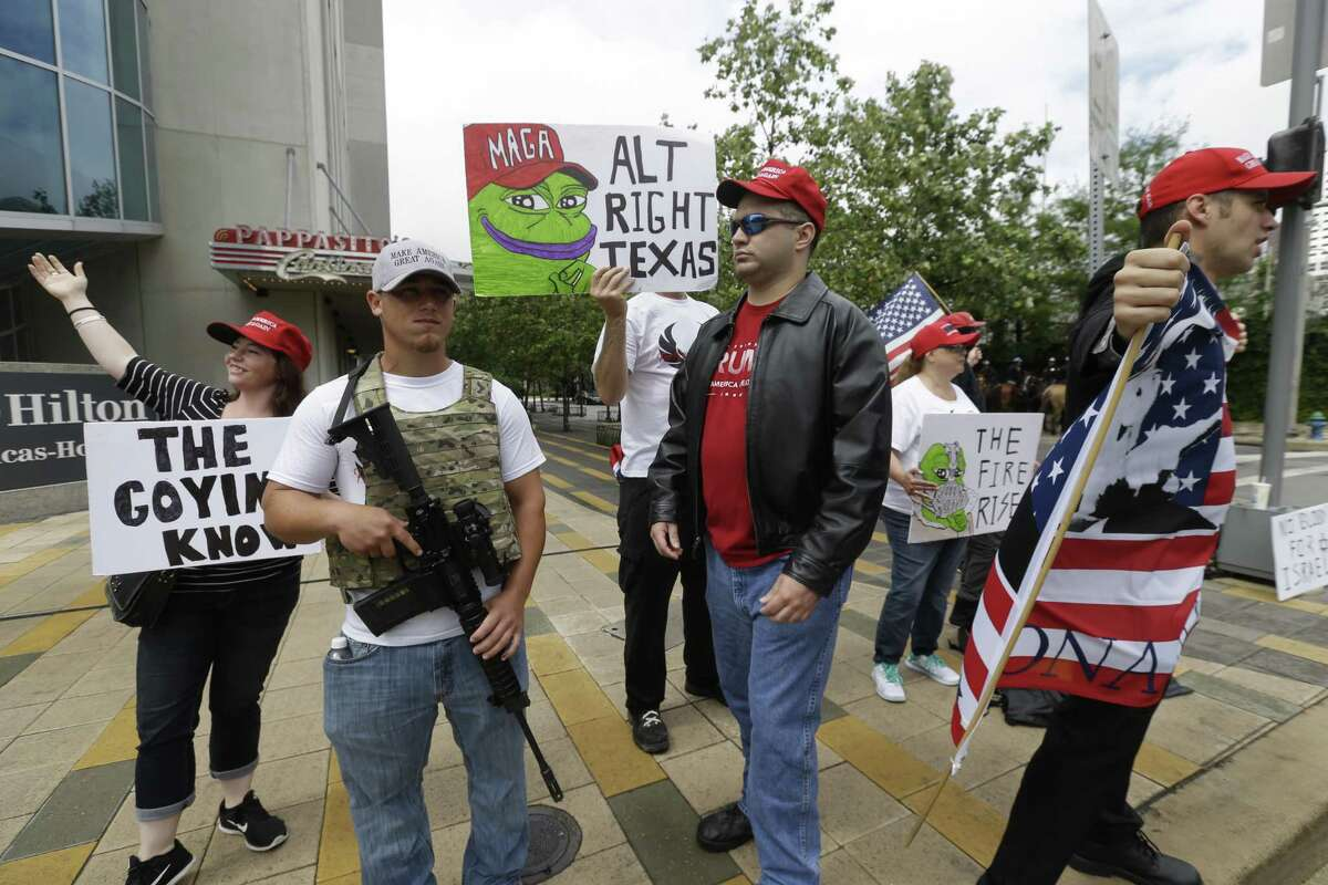 Protester groups representing both the far right and far left are shown outside the Hilton Americas where Governor Greg Abbott is scheduled to make a speech Tuesday, April 18, 2017.