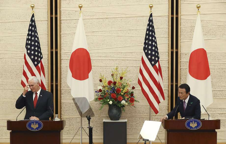 Mike Pence and Japanese Deputy Prime Minister Taro Aso listen to a question at a joint press conference. Photo: Eugene Hoshiko, Associated Press