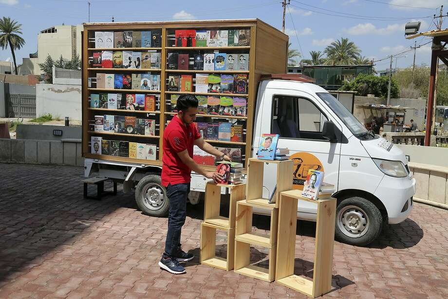 Ali al-Moussawi arranges his books on a street in Baghdad, which was once the literary capital of the Muslim world but is now better known for bombings. Photo: Karim Kadim, Associated Press