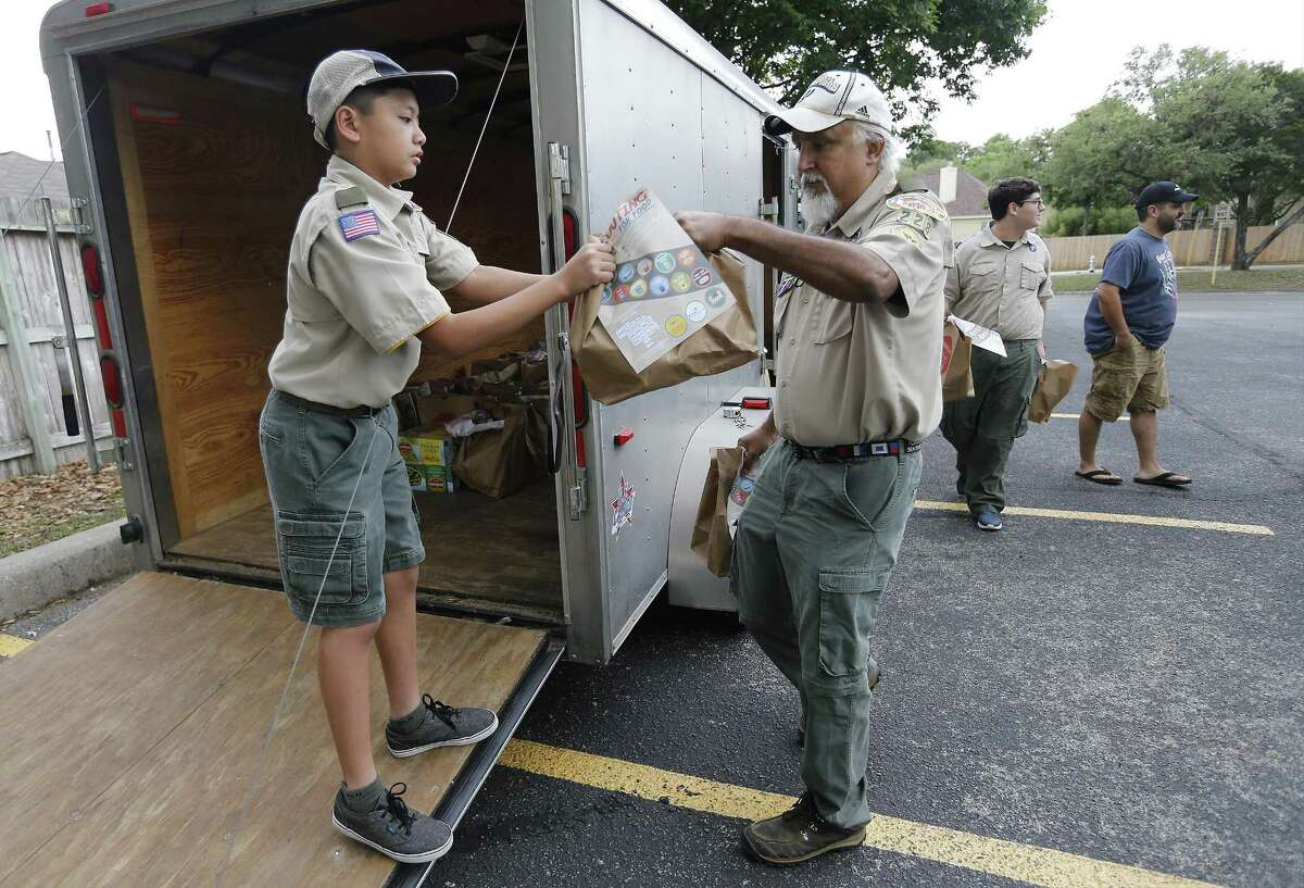 Troop 228 Boy Scout Kirk Cangco (left) takes a bag a food from Scout Leader Gilbert Lopez as Troop 228 collect bags of food for the San Antonio Food Bank as part of their community service on Saturday, Apr. 15, 2017. Earlier, Boy Scouts and Girl Scouts fanned out across the city, leaving 100,000 paper bags on doorsteps in many local neighborhoods, asking that the homeowners fill the bags with nonperishable foods for the Food Bank. On Saturday, these same scouts went back to pick up the filled bags and took them to various drop-off points for the food bank. Troop 228 Scout Leader Ben Peña said the troop taken part in the food drive for many years. (Kin Man Hui/San Antonio Express-News)