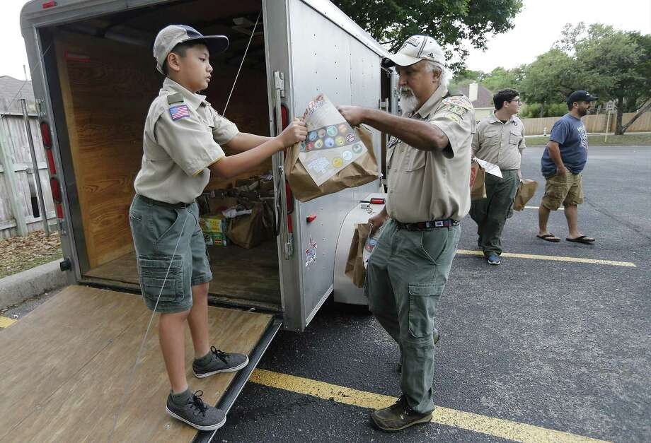 Troop 228 Boy Scout Kirk Cangco (left) takes a bag a food from Scout Leader Gilbert Lopez as Troop 228 collect bags of food for the San Antonio Food Bank as part of their community service on Saturday, Apr. 15, 2017. Earlier, Boy Scouts and Girl Scouts fanned out across the city, leaving 100,000 paper bags on doorsteps in many local neighborhoods, asking that the homeowners fill the bags with nonperishable foods for the Food Bank. On Saturday, these same scouts went back to pick up the filled bags and took them to various drop-off points for the food bank. Troop 228 Scout Leader Ben Peña said the troop taken part in the food drive for many years. (Kin Man Hui/San Antonio Express-News) Photo: Kin Man Hui, Staff / San Antonio Express-News / ©2017 San Antonio Express-News