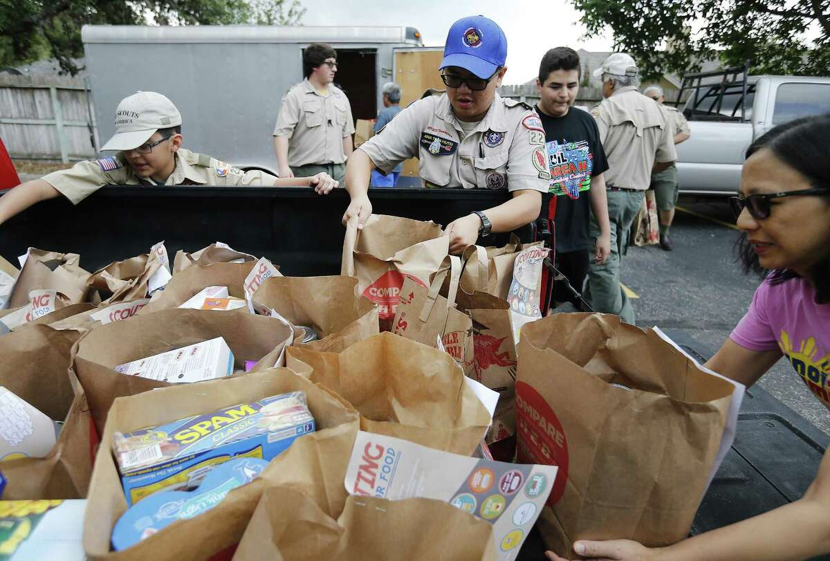 Troop 228 Boy Scouts Franz Cangco (center), who is an Eagle Scout, and Dylan Guzman (left) unload grocery sacks of nonperishable items. Groceries collected during the Scouting for Food drive go to the San Antonio Food Bank.