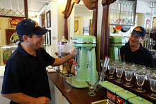 Mike Lisotta makes a milkshake with his vintage 1940s mixer at Mike's Old Fashioned Soda Fountain in downtown Port Neches on Friday. The city's small downtown area has seen an influx of new businesses trying to revitalize it over the past five years.  Photo taken Friday 4/14/17 Ryan Pelham/The Enterprise