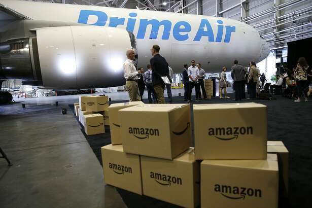 """FILE - In this Thursday, Aug. 4, 2016, file photo, Amazon.com boxes are shown stacked near a Boeing 767 Amazon """"Prime Air"""" cargo plane on display in a Boeing hangar in Seattle. Retail subscription programs, such as Amazon Prime, promise free shipping to members for a monthly or yearly fee. As shoppers demand speed, some cyberstores are offering free and fast shipping, albeit with minimum-purchase requirements. Certain situations, however, may warrant paying the membership fee. (AP Photo/Ted S. Warren, File)"""