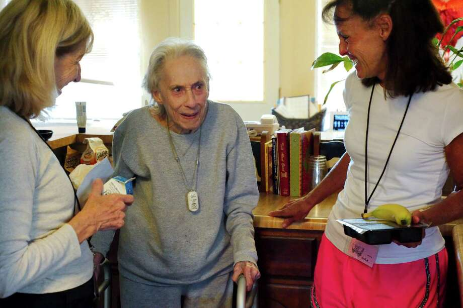 Bay Area Meals on Wheels volunteers Carol Gomez, left, and Lisa Ruchte, right , share a laugh with Lois McCormick, 90, as they deliver her daily meal in her home. Photo: Kirk Sides / © 2016 Kirk Sides / Houston Community Newspapers
