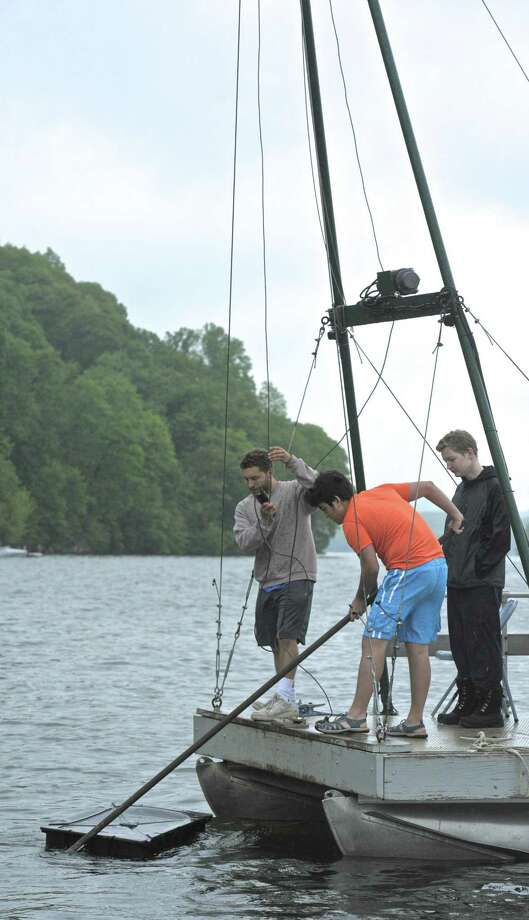 Joseph Reisman, left, Eamon Flaherty, 17, of New Fairfield, and Michael Barbera, 17, of New Fairfield, pull a dock float out of the water as part of the 15th Annual John Marsicano Memorial Lake Cleanup, on Saturday, May 16, 2015, in New Fairfield, Conn. Photo: H John Voorhees III / H John Voorhees III / The News-Times