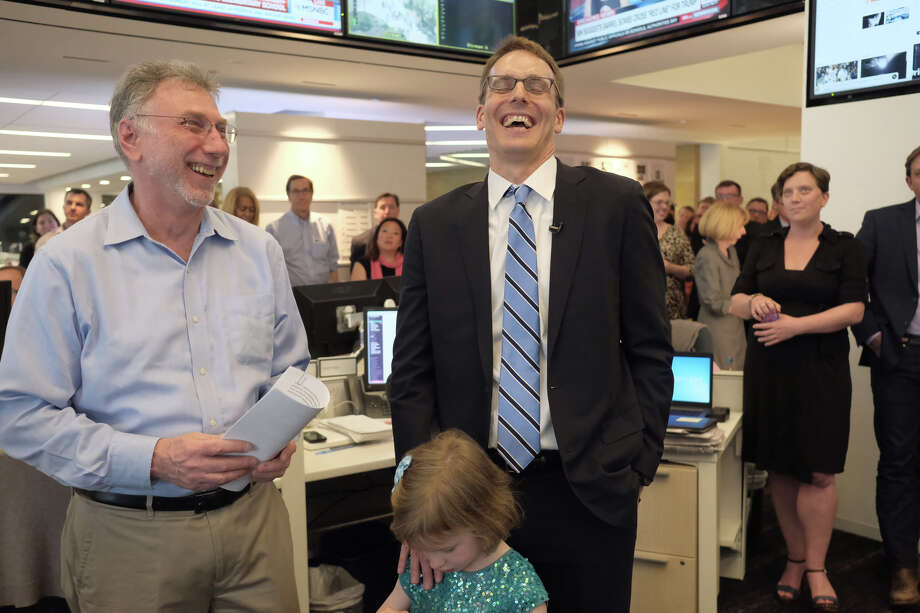 The Washington Post's Martin Baron, left, and David Fahrenthold react at the news of Fahrenthold's win of the Pulitzer Prize for National Reporting in the newsroom of the Washington Post in Washington on April 10, 2017.  Fahrenthold is a 1996 graduate of Memorial High School. / The Washington Post