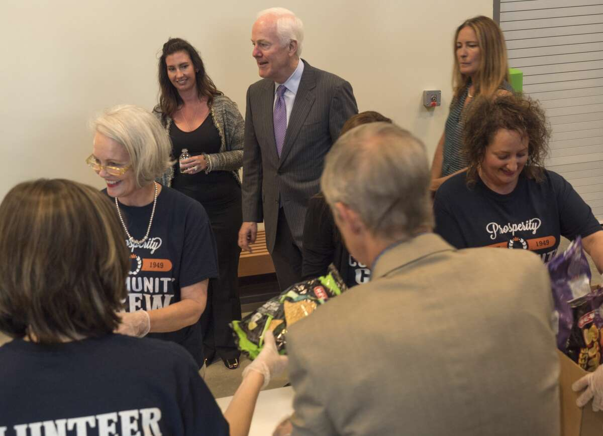 U.S. Sen. John Cornyn toured the West Texas Food Bank April 18 with Executive Director Libby Campbell, left, and Celia Cole, CEO of Feeding Texas, as volunteers sort bags of chips donated to the facility.