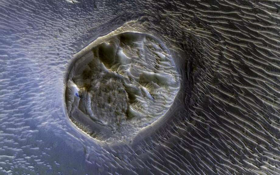 This image from NASA's Mars Reconnaissance Orbiter shows a small (0.4 kilometer) mesa, one of several surrounded by sand dunes in Noctis Labyrinthyus, an extensively fractured region on the western end of the Red Planet's Valles Marineris. The mesa resembles an ulcerated wound. Photo: NASA