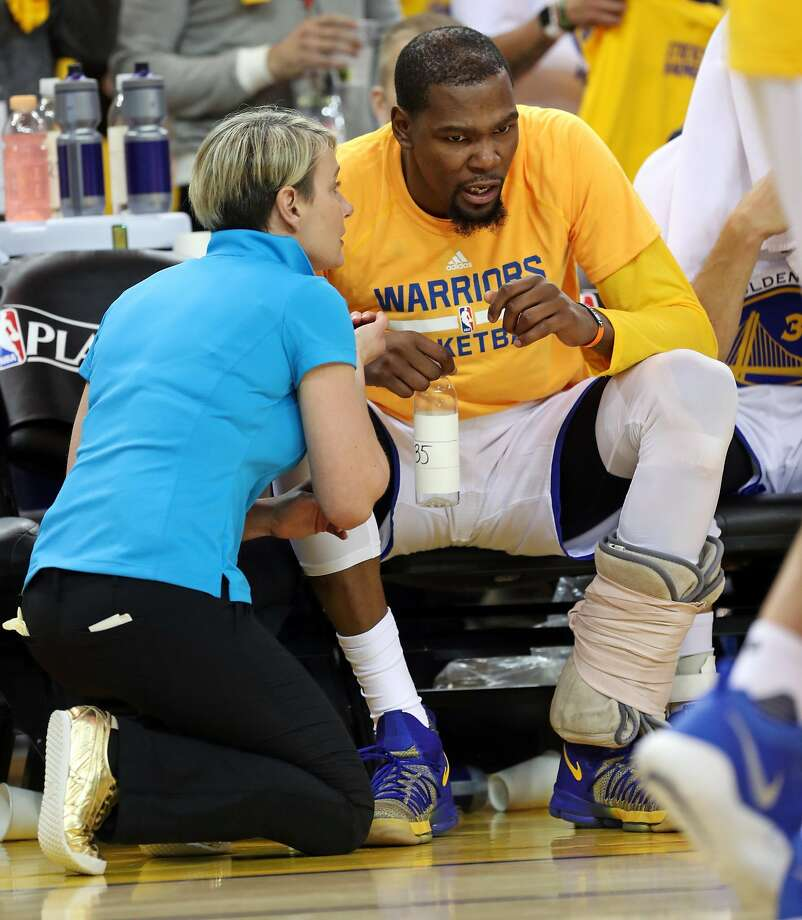 Golden State Warriors' Kevin Durant confers with trainer Chelsea Lane after straining his calf during Warriors' 121-109 win over Portland Trail Blazers in Game 1 of NBA Western Conference 1st Round Playoffs at Oracle Arena in Oakland, Calif., on Sunday, April 16, 2017. Photo: Scott Strazzante, The Chronicle