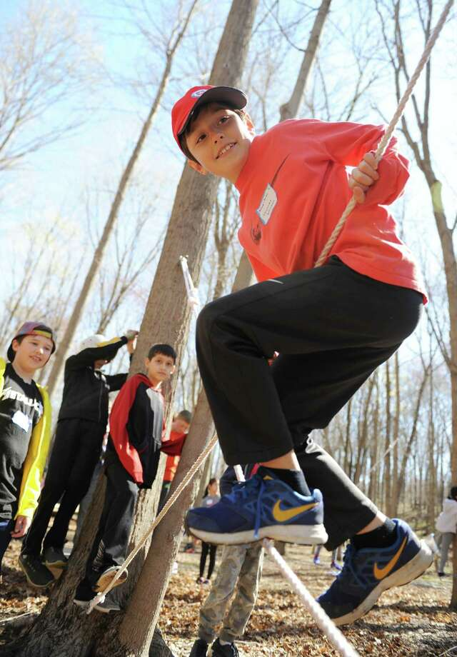 Julian Curtiss fifth-grader Thomas Johnson keeps his balance on a rope during Greenwich Public Schools' Orienteering Adventure Days at the Camp Seton Scout Reservation in Greenwich, Conn. Tuesday, April 18, 2017. Led by P.E. teachers and staff from Camp Seton Scout Reservation, all fifth graders from the eleven Greenwich Public Elementary Schools met and interacted with those students who will be in their sixth grade classes next year while participating in a variety of activities blending fitness, writing, map reading, and team building skills. Photo: Tyler Sizemore / Hearst Connecticut Media / Greenwich Time