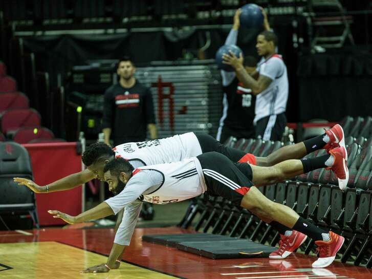 Basketball gives way to a bit of ballet as Rockets guard James Harden, foreground, and center Clint Capela loosen up before a workout at Toyota Center in anticipation of Game 2 tonight. In the background, other Rockets limber up with a different kind of ball.