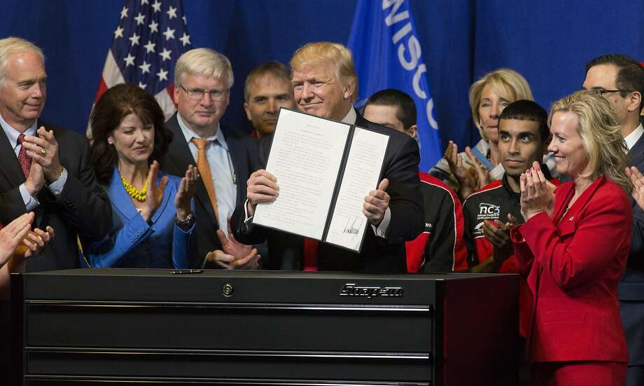 "President Donald Trump signs the so-called ""Buy American, Hire American"" executive order on Tuesday, April 18, 2017 during a visit to Snap-on Inc. in Kenosha, Wis. The orders clamp down on guest worker visas and require federal agencies to buy more goods and services from U.S. companies and workers. (Mark Hoffman/Milwaukee Journal Sentinel/TNS) Photo: Mark Hoffman, TNS"