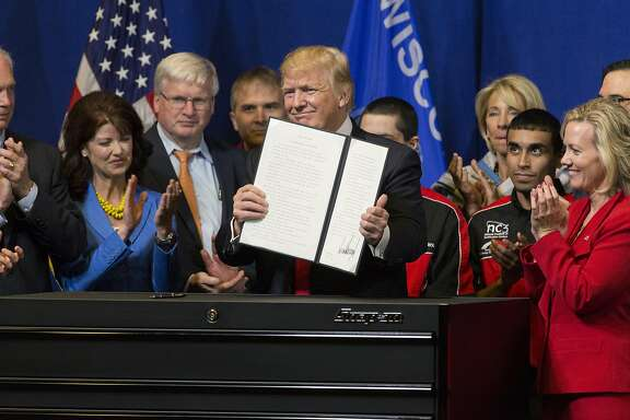 "President Donald Trump signs the so-called ""Buy American, Hire American"" executive order on Tuesday, April 18, 2017 during a visit to Snap-on Inc. in Kenosha, Wis. The orders clamp down on guest worker visas and require federal agencies to buy more goods and services from U.S. companies and workers. (Mark Hoffman/Milwaukee Journal Sentinel/TNS)"