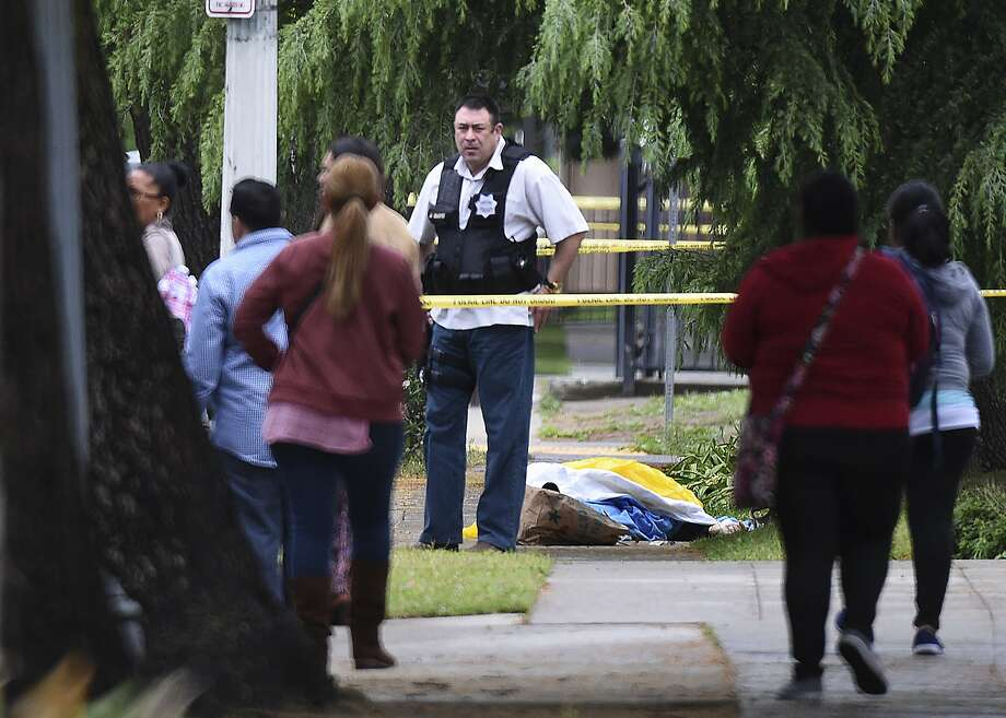 A police detective stands near the body of one of the three shooting victims in downtown Fresno. A 39-year-old man, Kori Ali  Muhammad, was taken into custody as a suspect in the killings. Photo: John Walker, Associated Press