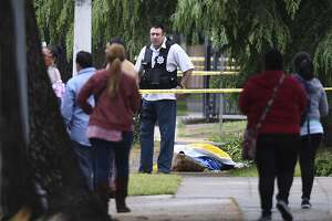 """A Fresno police detective stands over the body of one of the three shooting victims Tuesday, April 18, 2017 in Fresno, Calif. A man shot and killed three people on the streets of downtown Fresno on Tuesday, shouting """"God is great"""" in Arabic during at least one of the slayings and later telling police that he hates white people, authorities said. Kori Ali Muhammad, 39, was arrested shortly after the rampage, whose victims were all white, police said. He also was wanted in connection with another killing days earlier, in which a security guard was gunned down at a Fresno motel after responding to a disturbance.(John Walker/Fresno Bee via AP)"""