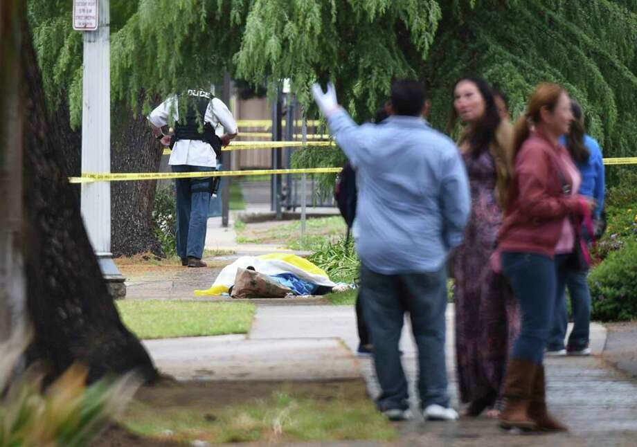 Evacuated office workers stand by, with a deceased shooting victim down on the sidewalk Tuesday, April 18, 2017 in Fresno, Calif. (John Walker/Fresno Bee via AP) Photo: John Walker, MBO / The Fresno Bee