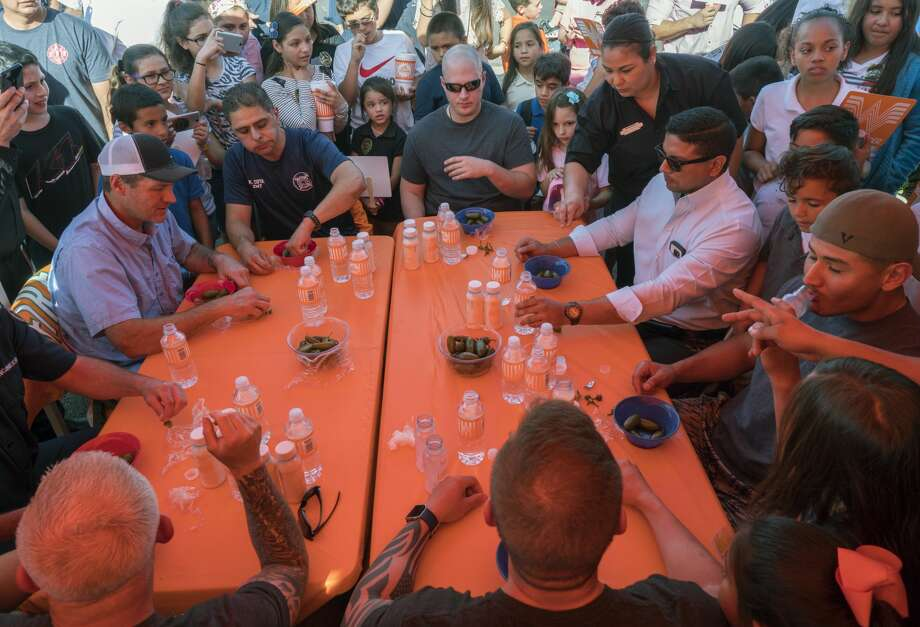 Members of the Midland Fire Department take on members of the Midland Police Department in a team event jalapeno eating contest 04-18-17 outside Whataburger on Big Spring. MPD's team ate 29 total jalapenos, earning their charity, Midland Boys and Girls Club, $1500. Tim Fischer/Reporter-Telegram Photo: Tim Fischer/Midland Reporter-Telegram