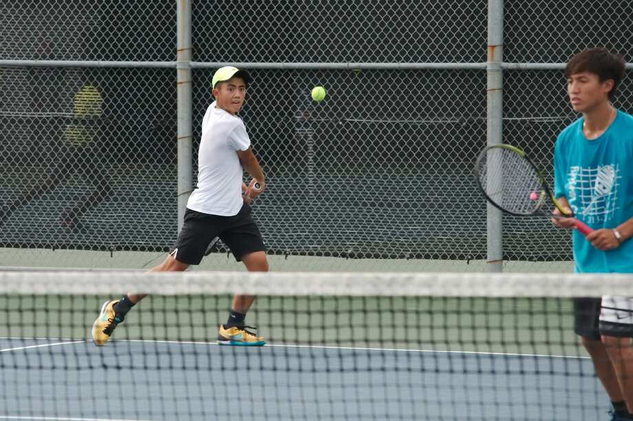 Ethan Bui of Friendswood prepares to hit a backhand Tuesday while teammate Johnny Luu looks on at the net in the Region III-6A tennis tournament in Deer Park. Bui and Luu defeated Dawson's Divyam Bansal and Jin Wang in a first-round match. Photo: Kirk Sides