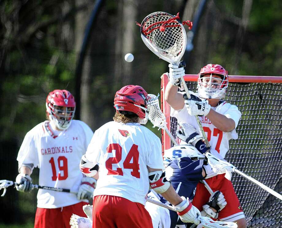 As teammate Bailey Savio (24) looks on, Greenwich goalie Andrew Triscari makes a stop on a point-blank shot by Ziggy Hallgarten of Staples during Monday's game at Greenwich High School. Photo: Bob Luckey Jr. / Hearst Connecticut Media / Greenwich Time