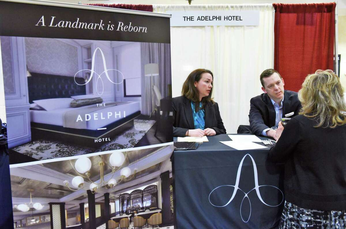 Adelphi hotel HR asst. Shannon Hubany, left, and director of housekeeping John Frazier speak a visitor to their booth during the Times Union job fair Tuesday April 18, 2017 in Colonie, NY. (John Carl D'Annibale / Times Union)