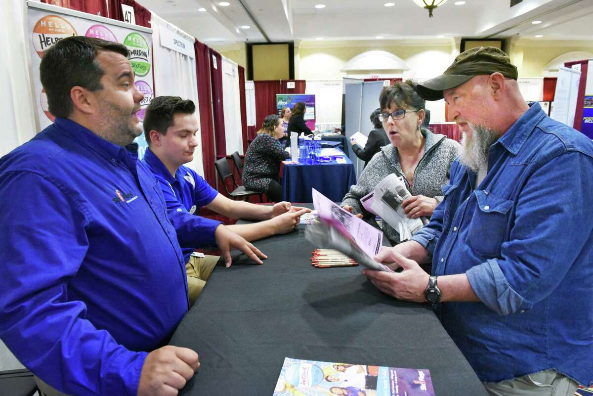 Six Flags America recruiters Bill Williams, left, and Wes Bessaw speak with job hunters Chris Mitchell of Colonie and Russell Brush, right, of Galway during the Times Union job fair Tuesday April 18, 2017 in Colonie, NY. (John Carl D'Annibale / Times Union)