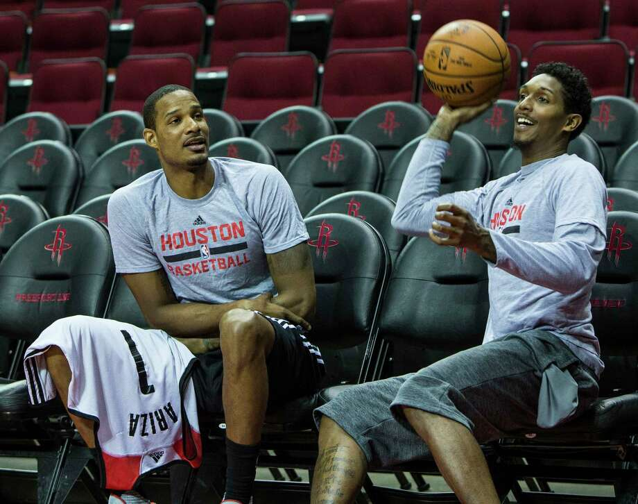 Rockets guard Lou Williams, right, tries a shot from the not-so-cheap seats as he and forward Trevor Ariza sit courtside Tuesday before practice at Toyota Center. Photo: Brett Coomer, Staff / © 2017 Houston Chronicle