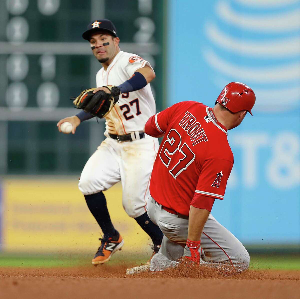 Los Angeles Angels Mike Trout (27) is tagged out at second base by Houston Astros second baseman Jose Altuve (27) as Albert Pujols ground into a double play during the seventh inning of an MLB baseball game at Minute Maid Park, Tuesday, April 18, 2017, in Houston.