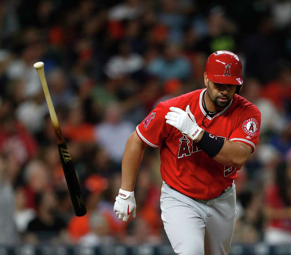 Los Angeles Angels designated hitter Albert Pujols (5) tosses his bat after hitting a three-run home run of of Astros starting pitcher Joe Musgrove during the fifth inning of an MLB baseball game at Minute Maid Park, Tuesday, April 18, 2017, in Houston.