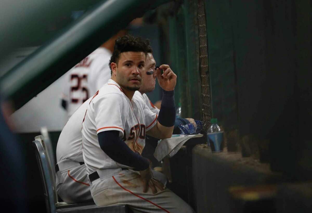 Houston Astros Jose Altuve (27) sits in the dugout watching Los Angeles Angels celebrate their 5-2 win after an MLB baseball game at Minute Maid Park, Tuesday, April 18, 2017, in Houston.