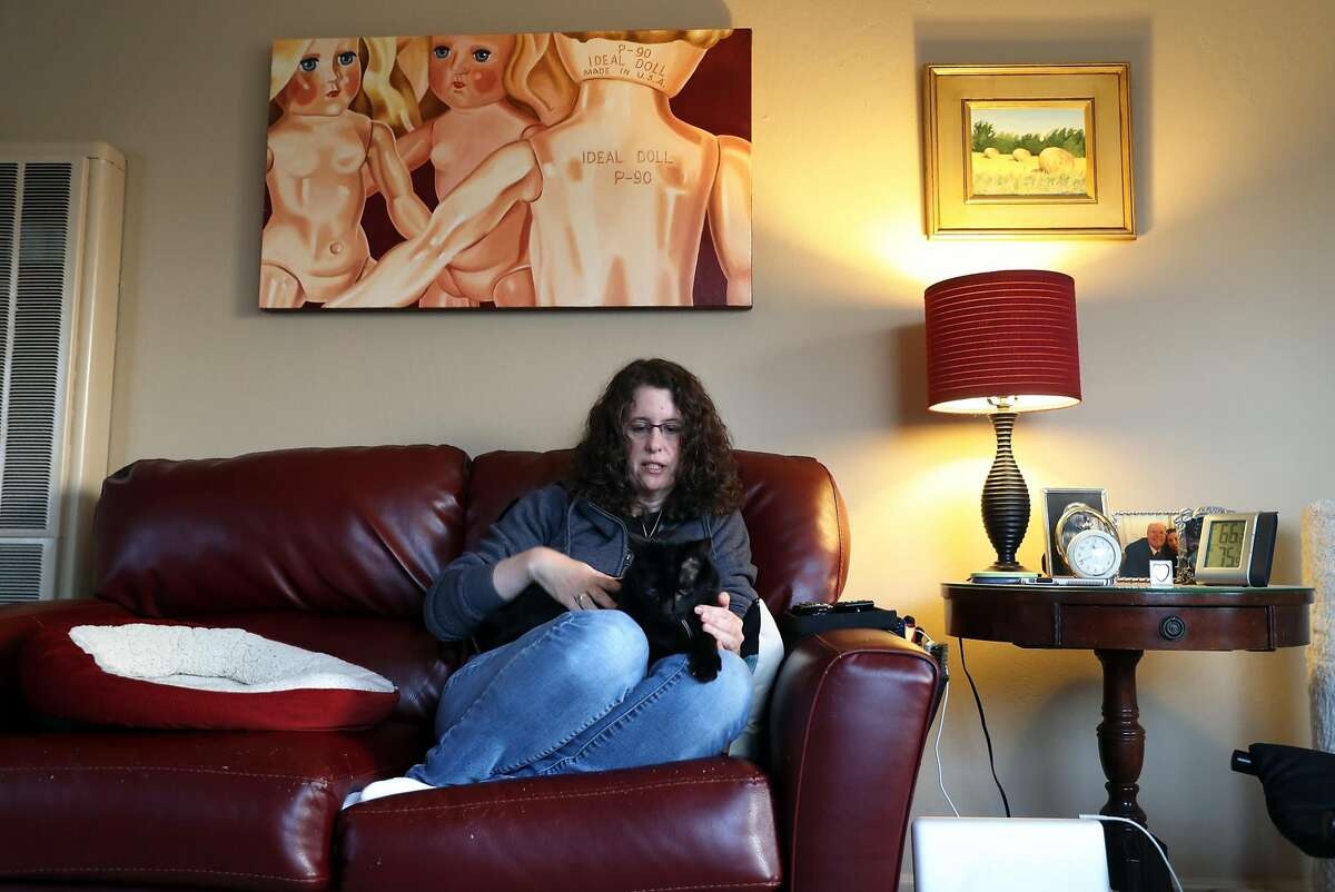 Amy Tucker relaxes with her cat, Dipper, at her apartment in Pacifica, Calif., on Tuesday, April 18, 2017. Tucker has had her rent raised $300 since April 1st.