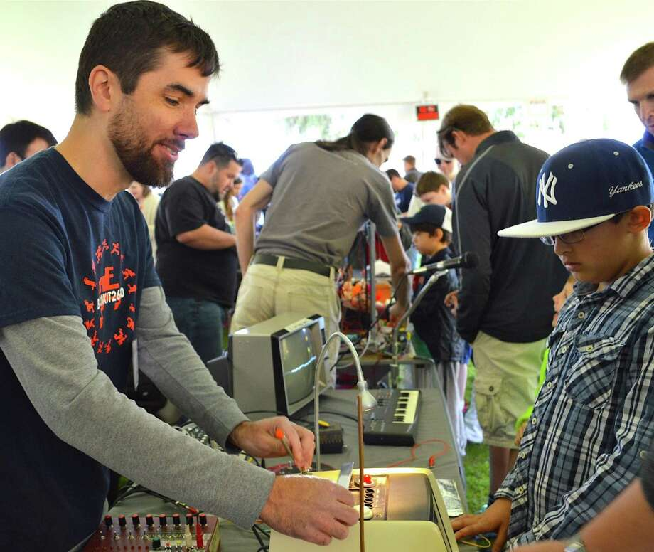 C.J. Basic, right, checks out the electronics that Thomas Uliasz designed and exhibited at the Westport Mini Maker Faire. Photo: Westport News / Jarret Liotta / Westport News