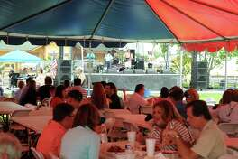 Guests sit under the tent as they eat crawfish and listen to zydeco music during the Rails and Tails Mudbug Festival in downtown Tomball. Photograph by David Hopper.