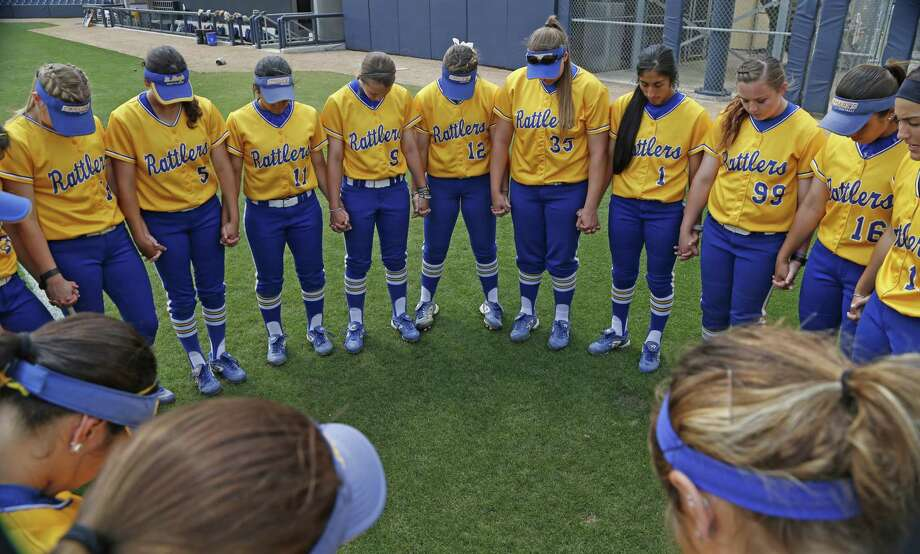 The St. Mary's Rattlers softball team gathers in prayer before the start of their game against Rogers State on March 24, 2017. Photo: Ron Cortes /For The Express-News / Freelance