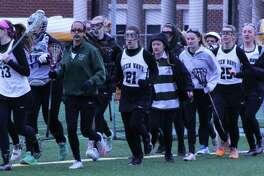 The New Milford High School girls' varsity lacrosse warm up before their April 1 seasoner opener against Granby Memorial High School.