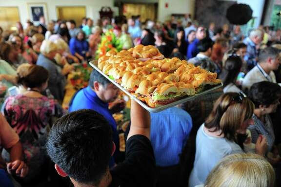 A caterer holds up a tray of Subway sandwiches for guests during the company's 50th anniversary celebration in its world headquarters in Milford, Conn. on Wednesday Aug. 27, 2015. The company announced in April 2017 that customers can now order through Facebook Messenger.