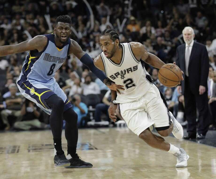 Spurs forward Kawhi Leonard drives around Memphis Grizzlies forward James Ennis III during the second half in Game 2 on April 17, 2017, in San Antonio. San Antonio won 96-82. Photo: Eric Gay /Associated Press / Copyright 2017 The Associated Press. All rights reserved.