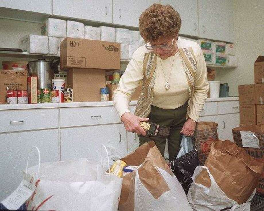 Biddy Roger, of Loaves & Fishes, standing in a supply room with arms full of donations in 1998. Photo: Hearst Connecticut Media File Photo