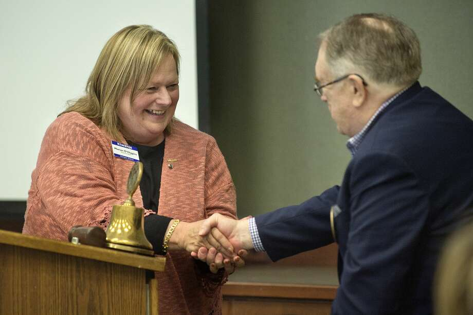 "BRITTNEY LOHMILLER | blohmiller@mdn.net Governor Elect Michigan District Marian O'Higgins, left, shakes hands with Kiwassee Kiwanis of Midland President Fred Honerkamp after presenting him with a 50th anniversary patch to go on the club's flag during the anniversary celebration at Trinity Lutheran Church Tuesday afternoon. ""You are the core of the community,"" O'Higgins said. The Kiwassee Kiwanis was started in 1967. Photo: Brittney Lohmiller/Midland Daily News/Brittney Lohmiller"
