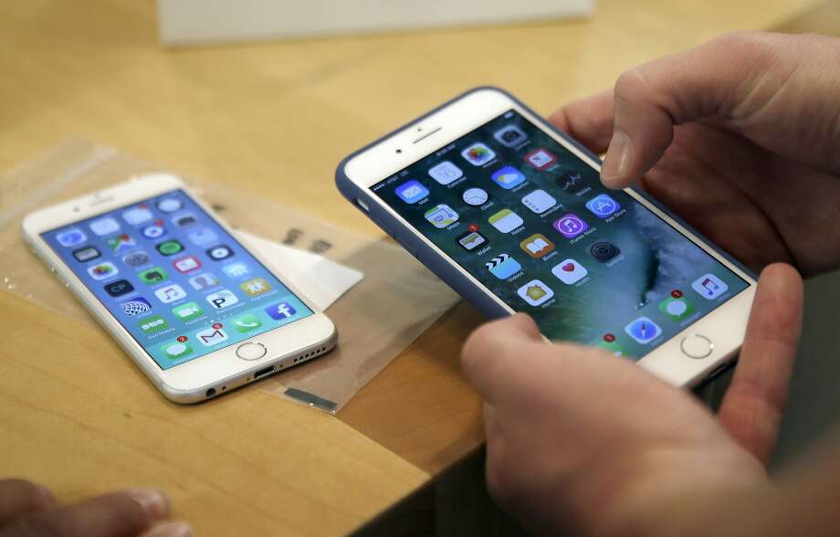 FILE - In this Friday, Sept. 16, 2016, file photo, a customer sets up his new iPhone 7 Plus, right, as he switches from the iPhone 6 at the Apple Store on Michigan Avenue during the release of the Apple iPhone 7 and the latest Apple Watches, in Chicago. New documents from WikiLeaks, posted Thursday, March 23, 2017, point to an apparent CIA program to hack Apple's iPhones and Mac computers such that the exploits persist even after the devices are reset to factory conditions. Security experts say the exploits are plausible, but they are playing down the threat to typical users. The techniques typically require physical access to devices, something the CIA would only use for individuals it is targeting. (AP Photo/Kiichiro Sato, File) Photo: Kiichiro Sato, Associated Press
