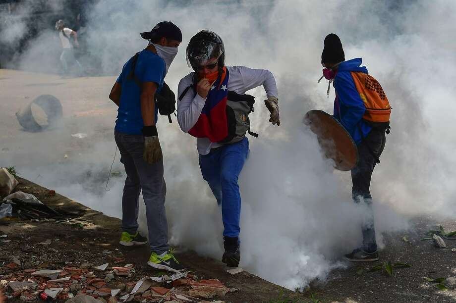 Opposition demonstrators clash with riot police officers during a protest against the government of Venezuelan President Nicolas Maduro in the capital, Caracas. Photo: RONALDO SCHEMIDT, AFP/Getty Images