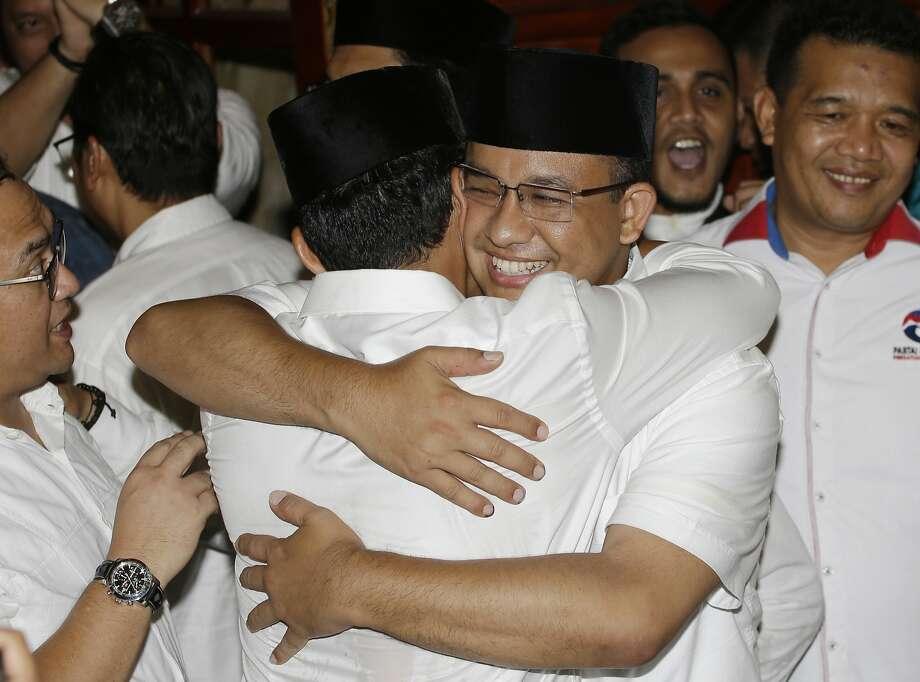 "Anies Baswedan (center right) hugs his running mate, Sandiaga Uno, after he defeated the capital city's minority Christian governor Basuki ""Ahok"" Tjahaja Purnama. Photo: Tatan Syuflana, Associated Press"