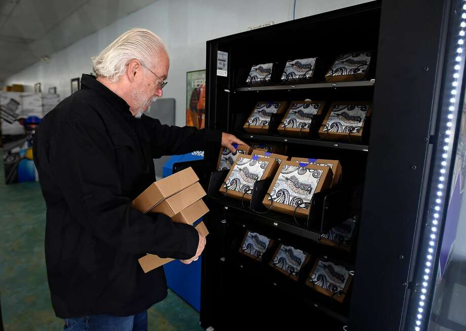 Health official Rick Reich loads needle kits onto a vending machine in Las Vegas. Users will have to register to receive a swipe card and ID number. Photo: David Becker, TNS