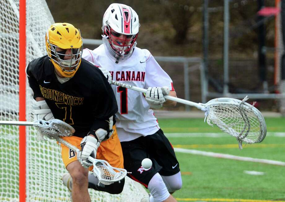 Brunswick's Alex Buckanavage, left, goes after the ball as New Canaan goalie Drew Morris gets drawn away from the net during their game Saturday in New Canaan. Photo: Christian Abraham / Hearst Connecticut Media / Connecticut Post