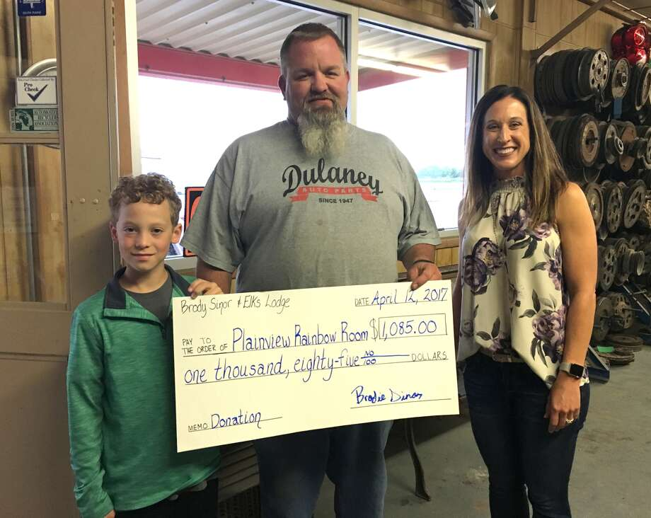 Coronado seventh grader Brodie Sinor and Plainview Elks Lodge Past Worshipful Master Cody Lindeman present a ceremonial $1,085 check to Rainbow Room representative Gretchen Massingill. The check represents proceeds of a raffle organized by Sinor to benefit the Rainbow Room.