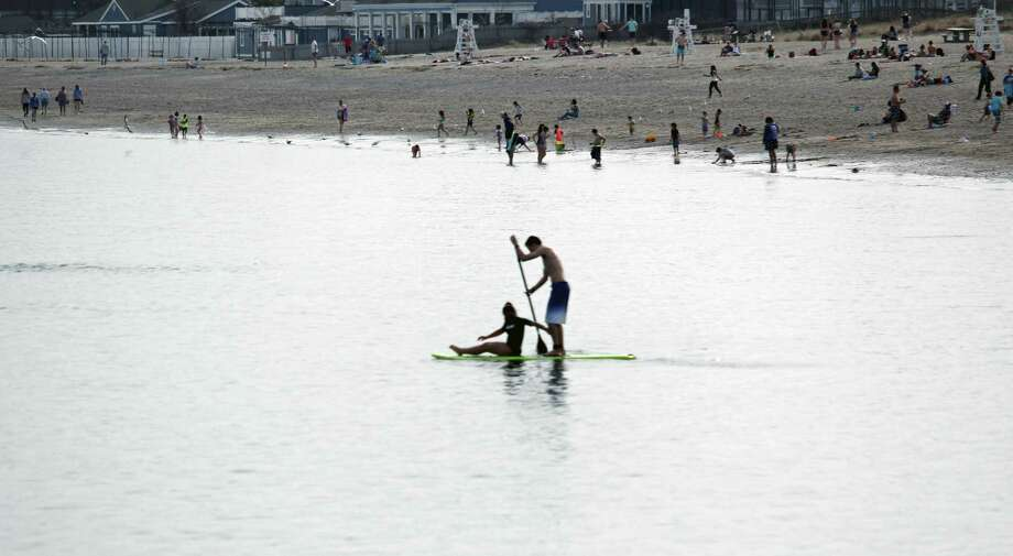 A paddle board duo takes to the water at Jennings Beach on April 11. Photo: Genevieve Reilly / Hearst Connecticut Media / Fairfield Citizen