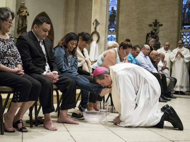 Archbishop Gustavo Garcia-Siller washes the feet of Alyssa Camarena and 11 other San Antonians at the San Fernando Cathedral mass during Holy Week in the Catholic faith in San Antonio, Texas on Thursday, April 13, 2017.