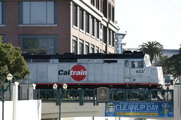 Caltrain rolls past the Box, Inc. headquarters office building located next to the train station in Redwood City, Calif. on Wednesday, April 19, 2017. Box is one of a few companies that has relocated to more transit-friendly environs and provides free Caltrain transit passes to its employees.